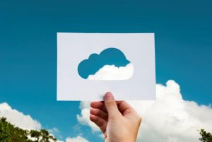 Hand mit Papier mit ausgeschnittener Wolke vor Himmel