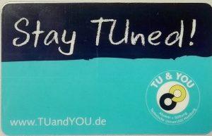 Die Vorderseite des Bibliotheksausweises zeigt vor blauem Hintergrund die Worte 'Stay TUned'.