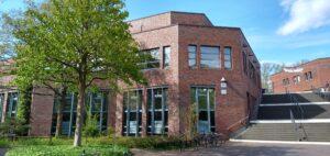 Die Bibliothek unter blauem Himmel. Ein Baum steht im Vordergrund.