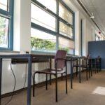Eine Reihe Arbeitstische mit Stühlen vor einer Fensterwand.